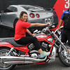 Kerri Atwood gets to sit on a Harley Davidson, compliments of Universal Technical Institute who was visting Camp Bulldog at Lynn English High School today. Behind her is Dan poor from the Institute. Photo by Owen O'Rourke