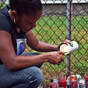 Latisha Payne lights a candle at a vigil for her brother, Brandon Payne, on the one year anniversary of his death on Tuesday, July 23. Item Photo / Angela Owens.