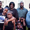 From left, Bradnon Payne's brother, Terrel Payne, sister, LaTisha Payne, mother, Lolita Miller, brother, OC Payne III, father, OC Payne Jr., and Brandon Payne's three children, Brandon Payne Jr., General Payne, and Aniyah Payne pose for a photo during a vigil on the one year anniversary of his death on Tuesday, July 23. Item Photo / Angela Owens.