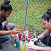 LaTisha Payne and Dee Rivera light candles at a vigil on the one year anniversary of Brandon Payne's death, on Tuesday, July 23. Item Photo / Angela Owens.