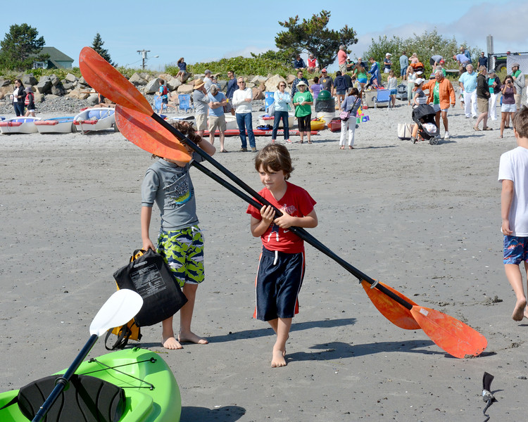 Nahant.  Short Beach.  <br /> Atticus Krauter, Nahant, aged 5 with oars three times bigger than he is, heads to a kayak as they line up on that start line.