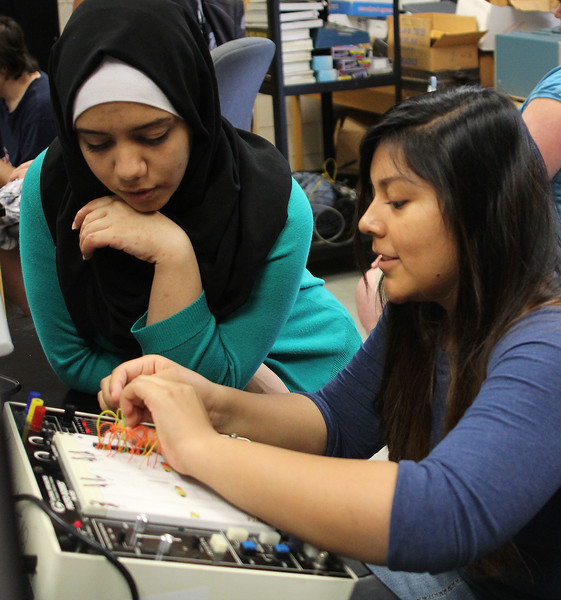 Rwan Rajab,, left, a student mentor, and Darlee Chavez from Lynn English High School, run tests on a proto board in an engineering class held at Norht Shore Community College this summer. Photo by Owen O'Rourke