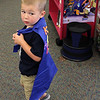 Kevin Geary tires on the super hero cape he made in the children's room at the Lynnfield Public Library. Photo by Owen O'Rourke