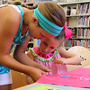 Kelsey and Ella Hodsdon build a super hero cape in the children's room at the Lynnfield Public Library today. Photo by Owen O'Rourke