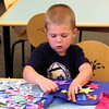 Kevin Geary in the process of building a super hero cape in the children's room at the Lynnfield Public Library today. Photo by Owen O'Rourke