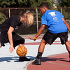 Tyler Farragamo dribbles, guarded by Juan Prenza, during Part of the Solution's Summer Slam basketball tournament at the Warren Street Playground on Thursday, August 16. Item Photo / Angela Owens.