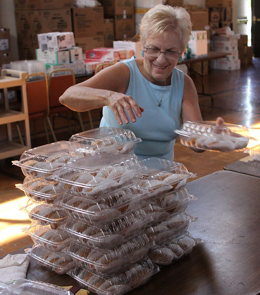 Elena Krios arranging boxesd of finikia that will be for sale at the Grecian Festival at St. George Orthodox  Church in Lynn this weekend. The Festival starts on Friday at 6pm until midnight, and resumes on both Saturday and Sunday from noon until midnight. Photo by Owen O'Rourke
