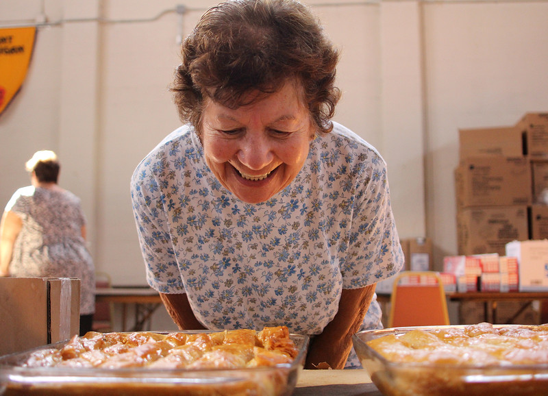 Connie Soteropoulos smelling some freshly made galaktoboureko that, along with many other homemade baked goods, will be sold a the annual Grecian Festival at St. George Orthodox Church across from Lynn Common starting Friday from 6pm to Midnight, and resuming both Saturday and Sunday from noon to midnight. Photo by Owen O'Rourke