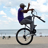 "Revere. Revere Beach. Eardley Earl Marcellus of Revere, rides a one wheeled bike along the wall that separates the beach from the pavement. He had ridden at least a mile by the time this picture was taken.  Why? ""Because it's fun"""