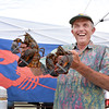 Marblehead, Farmer's Market Saturday morning.<br /> Paul Crowell, born in Marblehead, living in Salem, holds up two lobsters he had for sale.  Crowell's lobster boat is moored in Marblehead harbor. Lobstering is average for this time of year, according to Crowell.