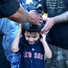 """Domenic Singer, aged 5, of Revere, tries on a night vision helmet used by the SWAT team. Helping him put it on are Officer John Cafarelli on the lft and his father Joe Singer, a school resource officer. They are at the """"National Night Out"""" event at the AC Whelan Elementary School."""
