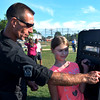 """Kamryn DiSisto, Revere, is shown how to hold a ballistic shield by Officer John Cafarelli, a member of Revere Police Department. She is attending """"National Night Out"""" , an event involving the police and the community.  They are at the AC Whelan Elementary School, Revere."""