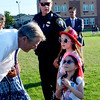 """Gov. Charlie Baker chats with Marisa (pink helmet) and Pina(red helmet) Yee of Revere . Behind them is Revere Police Chief Joseph Cafarelli.  They are at the """"National Night Out"""" event where the community and the police get together."""