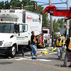 Workers minutes after righting this truck which was on ists side after being struck by anotehr truck while taking a right on North Shore Road at Oak Island Street in Revere today at 10 am. Photo by Owen O'Rourke