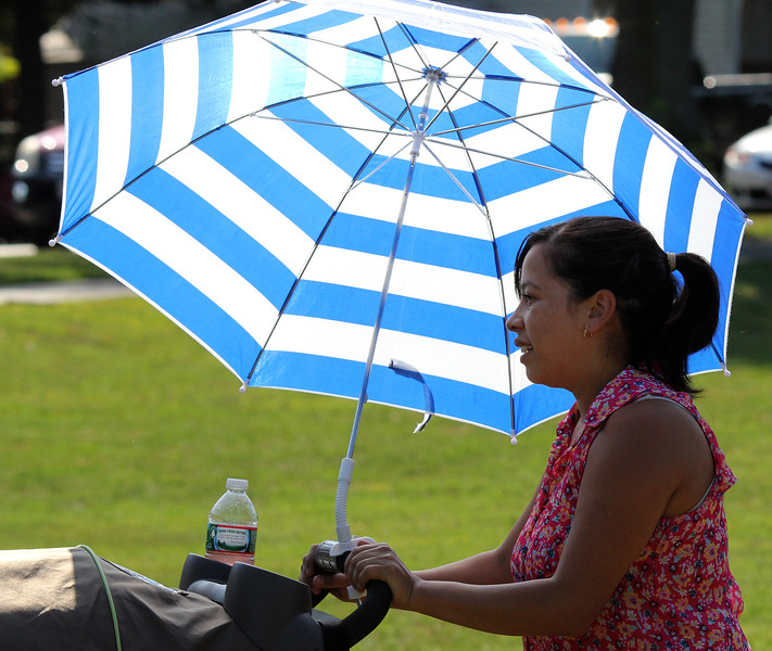 Silvia Velasquez was one of the people to use an umbrella at the Family and Children's Service of Greater Lynn annual outing on Lynn Common today. Photo by Owen O'Rourke