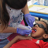 Daniel Acevedo gets his teeth polished by Valerie Osborn of the Polished, LLC group at the Family and Children's Service of Greater Lynn annual outing on Lynn Common today. Photo by Owen O'Rourke