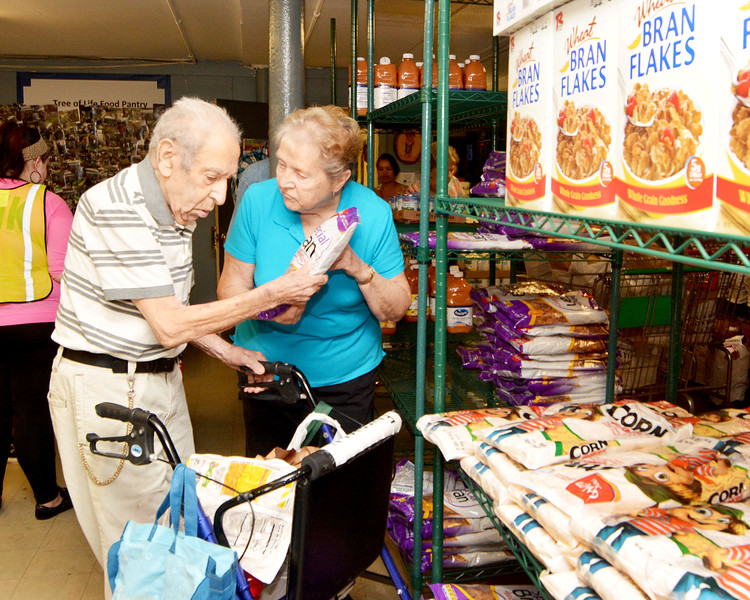 Lynn. St. Mary's Chapel. Food Pantry Closing. The last Day.   Josif Febermen, aged 90, Lynn, selects a breakfast cereal with the help of June Pagano, Lynn, a volunteer at the pantry.