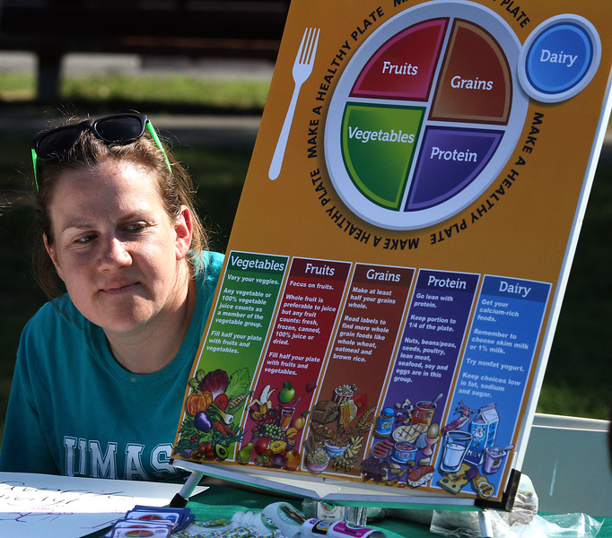 Elizabeth Dewey at  the grow healthy together chart at the U Mass Extension table at the Family and Children's Service of Greater Lynn annual outing on Lynn Common today. Photo by Owen O'Rourke