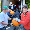 Saugus, First Congregational Church.  Pumpkin delivery <br /> Darin Leahy, Stoneham, passes a pumpkin to Rev. Martha Leahy, the church pastor.  Several brigades were formed to unload the truck that brought the pumpkins from New Mexico.