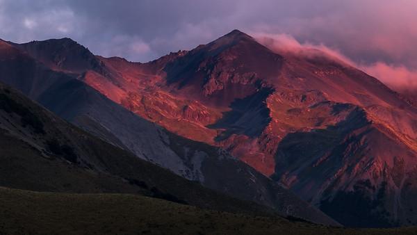 Early morning sun rays begin to envelop the Mount Enys mountain range near SH73.