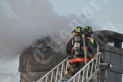 Bar Harbor firefighters work to extinguish a stubborn chimney fire at the Harborside Hotel on West Street in Bar Harbor on Tuesday evening. No major damage was reported. ISLANDER PHOTO BY EARL BRECHLIN