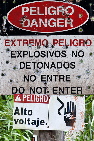 Bullet riddled warning sign for undetonated explosives.