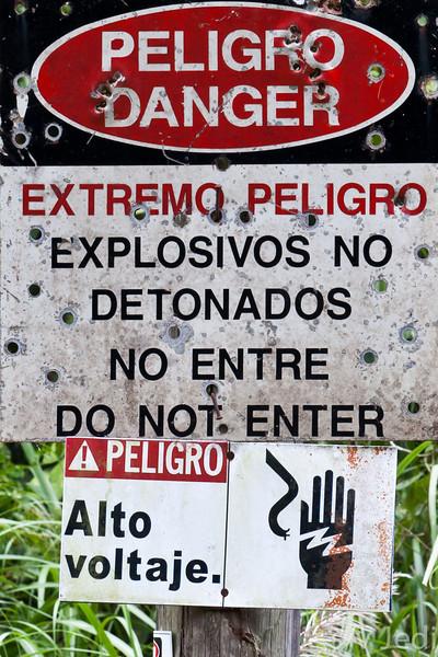 Bullet riddled warning sign for undetonated explosives.