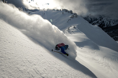 "Throwing up a large plume of powder, this skier is about to get a highly sought after ""faceshot"""