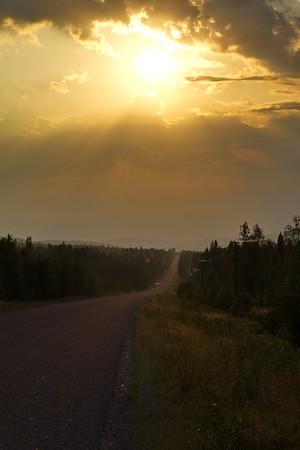 Väg 348 nära Bredbyn - Setting sun glowing over a country road