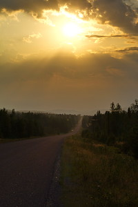 Setting sun glowing over a country road