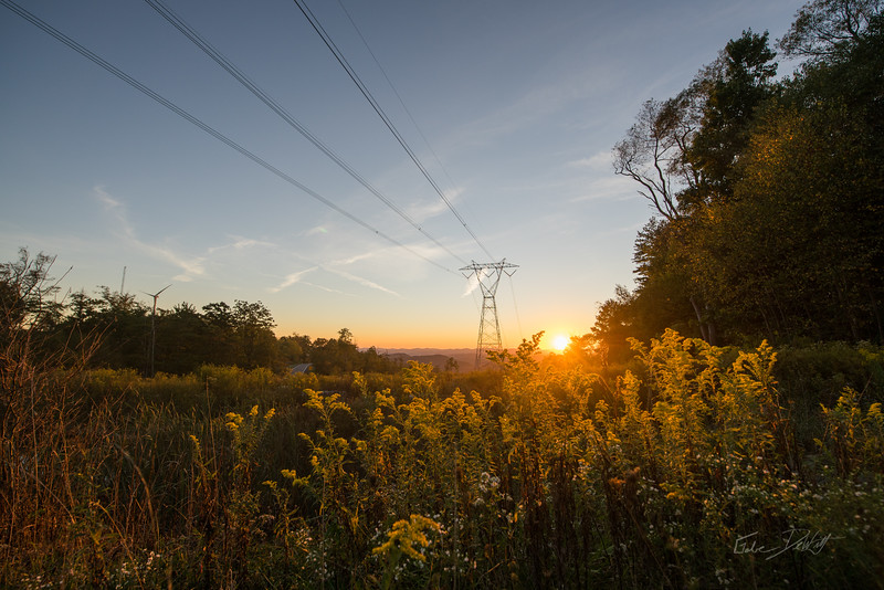 Along the central Appalachian ridge of Backbone Mountain, West Virginia, the setting sun silhouettes the Allegheny Power Transmission System in the Monongahela National Forest.