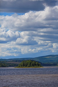 Island in a lake on a summer day with towering clouds