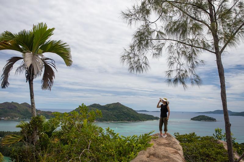 A female tourist overlooking Baie St Anna on Praslin island in the Seychelles.
