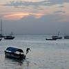 Locals swimming from a boat near the Stone Town shore at sunset in Zanzibar, Tanzania.