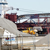 WARREN DILLAWAY / Star Beacon<br /> STONE IS moved by heavy equipment adjacent  to a large ship docked in Conneaut Harbor on Monday afternoon.