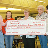 WARREN DILLAWAY / Star Beacon<br /> GARY HEAVEN, and his wife Debbie, present a $5,000 check to representatives of Hospice of the Western Reserve (from right)  Sue Legg, Mary Pepperney and Cathy Westcott  during the Ashtabula County Board of Realtors Cake Auction at the Ashtabula Towne Square on Saturday.