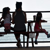 WARREN DILLAWAY / Star Beacon<br /> CHRISTY WISOR (center) and her daughters Ava (left) and Alie are silhouetted while eating lunch at Lake Shore Park in Ashtabula Township on Monday.