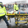 """WARREN DILLAWAY / Star Beacon<br /> COMMUNITY CARE Ambulance workers take a """"mock crash victim"""" from the Pymatuning Valley High School parking lot with Ohio State Highway Patrol Trooper Scott Balcomb (center) looking on Friday afternoon in Andover Township."""