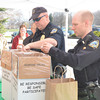 WARREN DILLAWAY / Star Beacon<br /> ASHTABUA POLICE officers Jason Erwin (right) and Tim Hoskins collect outdated or no longer needed prescription drugs from the public on Saturday during an Ashtabula County Medical Center Health Fair at Kent State University-Ashtabula Campus.