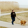 WARREN DILLAWAY / Star Beacon<br /> ALEXIA SUTTER of Madison walks her dog Ruthie along the bike path near the Geneva State Park Marina.