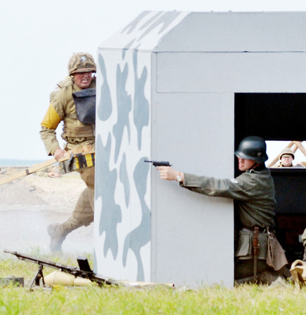 WARREN DILLAWAY / Star Beacon<br /> AN AMERICAN soldier (left) invades a German position during D-Day Conneaut on Saturday at Conneaut Township Park.