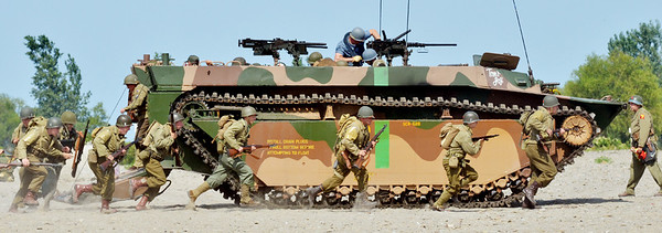 WARREN DILLAWAY / Star Beacon<br /> WORLD WAR II re-enactors race from a tank on Saturday during D-Day Conneaut.