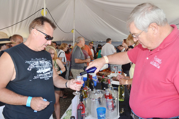 WARREN DILLAWAY / Star Beacon<br /> HERB BIAS, a volunteer with Debonne Vineyards, pourrs a glass of wine for Tim Raines of Erie during the Wine and Walleye Festival in Ashtabula Harbor on Saturday.