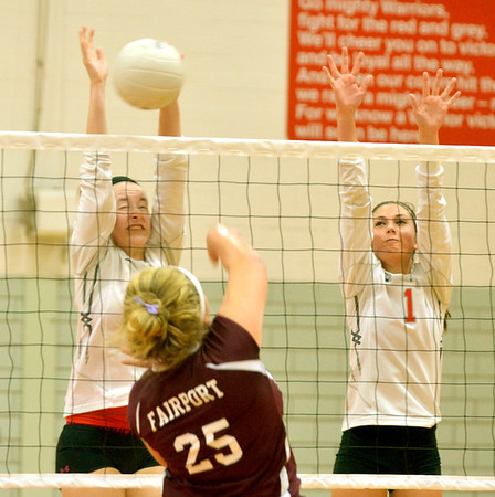 WARREN DILLAWAY / Star Beacon<br /> ALYSSA JOHNSON (left facing) and Karli Kanicki, both of Edgewood, leap for a block of a spike by Lauren Bodi of Fairport on Monday at Edgewood.