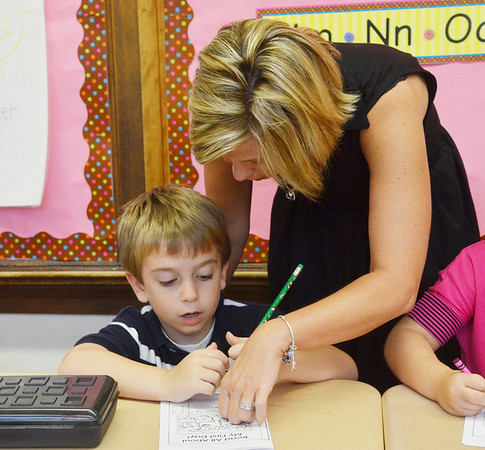 WARREN DILLAWAY / Star Beacon<br /> FIRST GRADE Teacher Terri Santee works with Jonathan Loomis on Tuesday during the first day of school at Kingsville Elementary School.