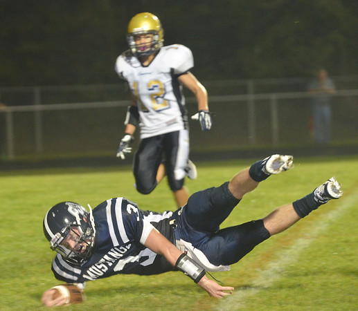 WARREN DILLAWAY / Star Beacon<br /> JAKE VORMELKER, Grand Valley quarterback leans across the goal line for a touchdown on Friday night in front of Isaiah Ngraingas of Conneaut at Orwell.