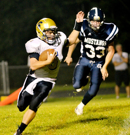 WARREN DILLAWAY / Star Beacon<br /> TROY COLUCCI of Conneaut runs for a touchdown with Tyler Zsigray of Grand Valley in hot pursuit on Friday night in Orwell.
