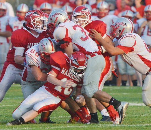 WARREN DILLAWAY / Star Beacon<br /> AARON ROSSI (33 center standing) of Geneva is swamped by Edgewood tacklers on Friday night at Corlew Stadium.