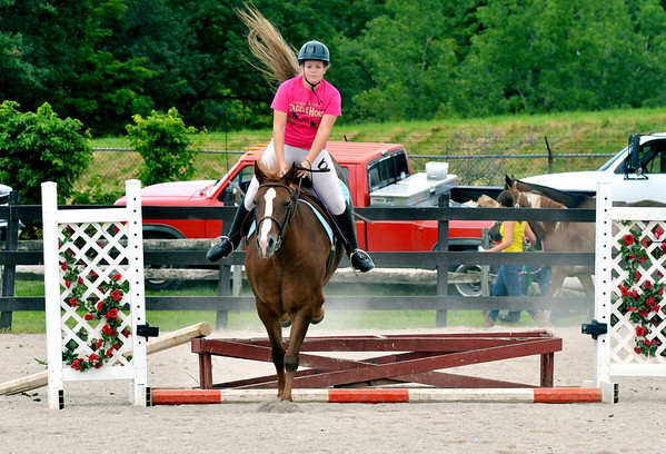 WARREN DILLAWAY / Star Beacon<br /> CLAIRE DODRILL, 18, of Harpersfield Township, works on the Steeplechase with her horse Amazie Grace on Monday at the Ashtabula County Fairgrounds in Jefferson. The horse competition at the fair begins this morning.