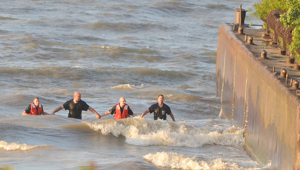 WARREN DILLAWAY / Star Beacon<br /> RESCUE WORKERS form a human chain along the shroreline of Lake Erie while looking for an apparent missing swimmer along Lake Road West in Saybrook Township Friday evening.